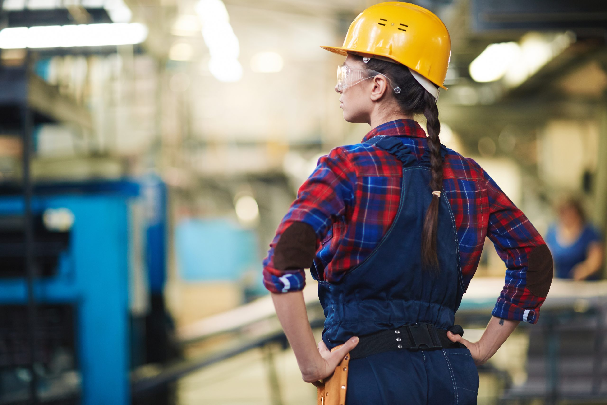 Female engineer in helmet controlling the process