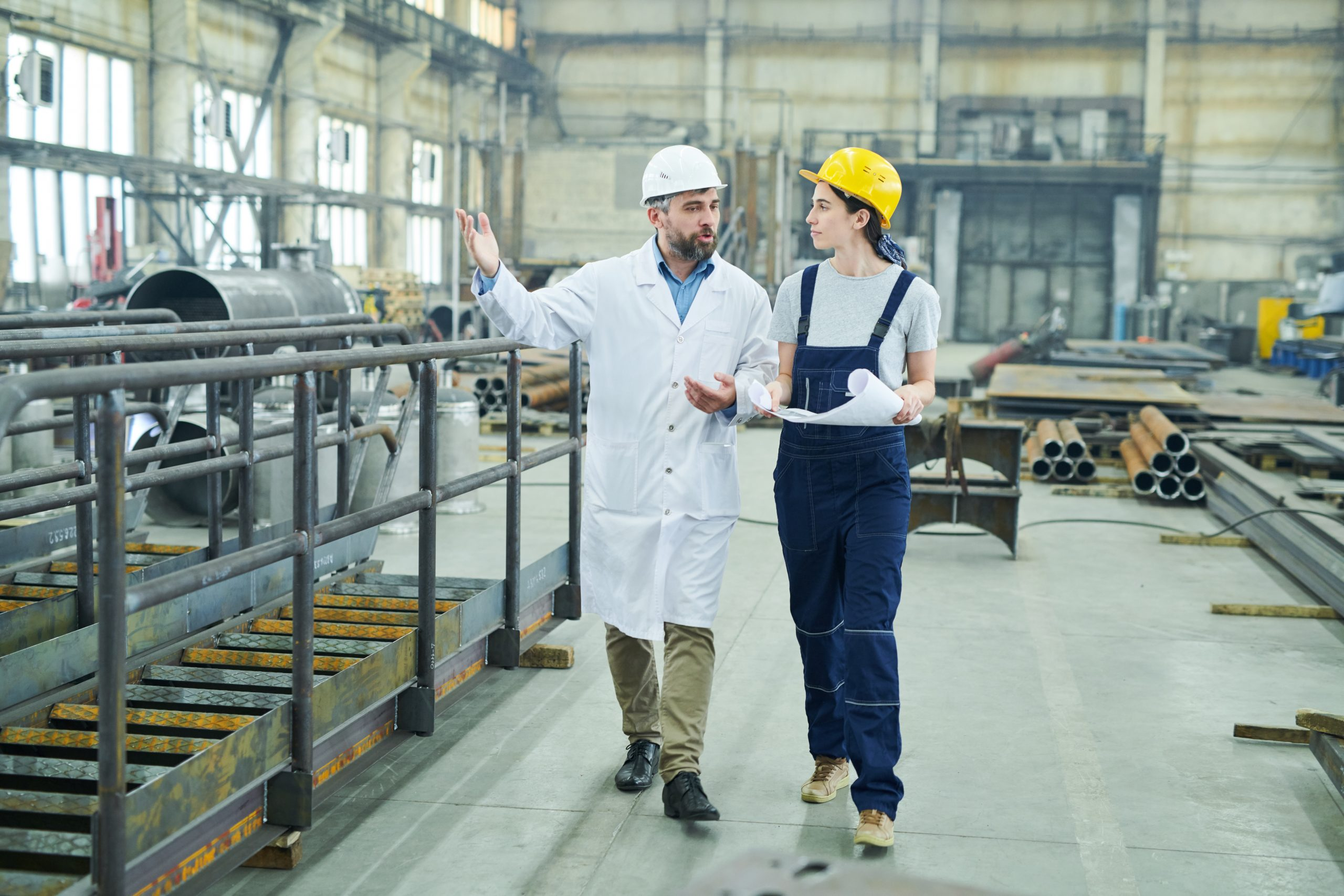 Full length portrait of female factory worker discussing plans with mature engineer while walking  in workshop, copy space