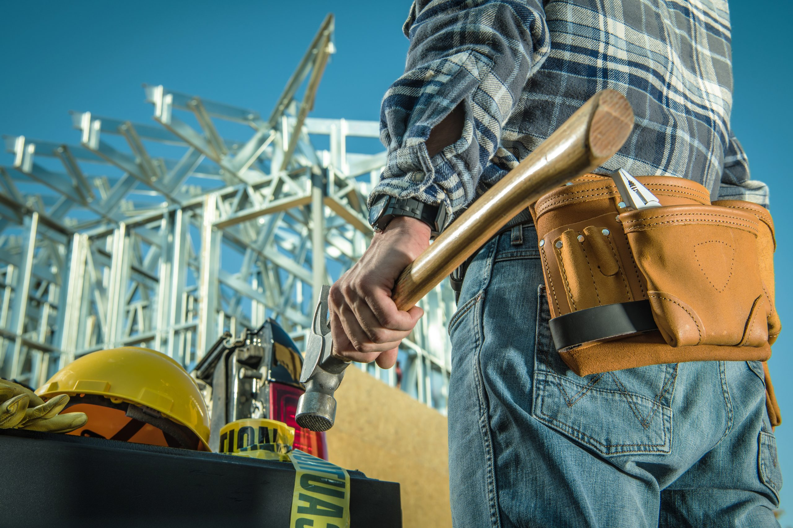 Caucasian Steel Construction Worker with Large Professional Hammer in Front of Construction Site.